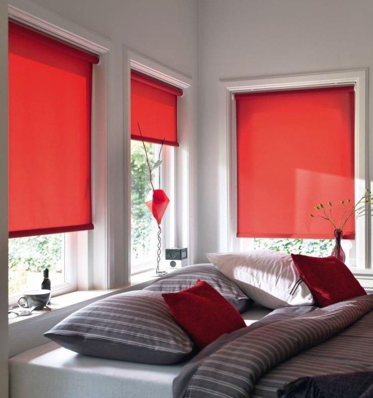 Интерьер спальни с красными рулонными шторами