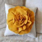 Белая подущка с оранжевым цветком