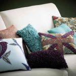 Белый диван, украшенный самодельными декоративными подушками