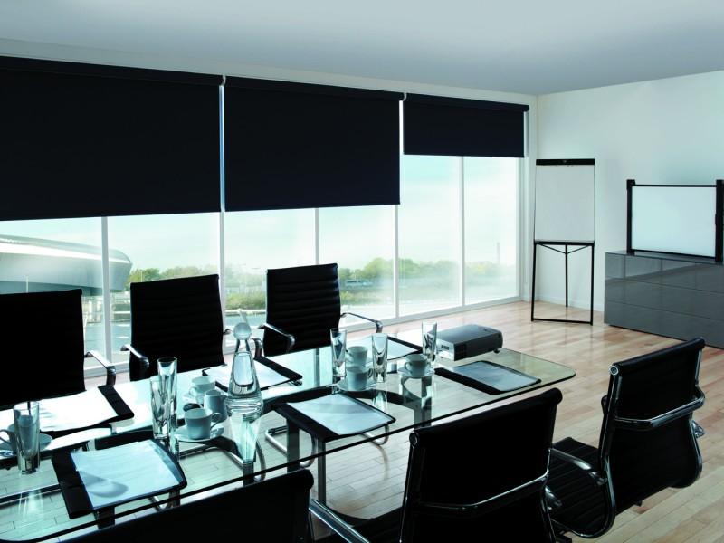 Черные шторы рулонного типа в переговорной комнате