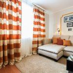 Шторы в оранжевую полоску в гостиной с угловым диваном