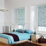 Оформление рулонными шторами окон в белой спальне