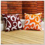 Коричневая и оранжевая подушки с завитками