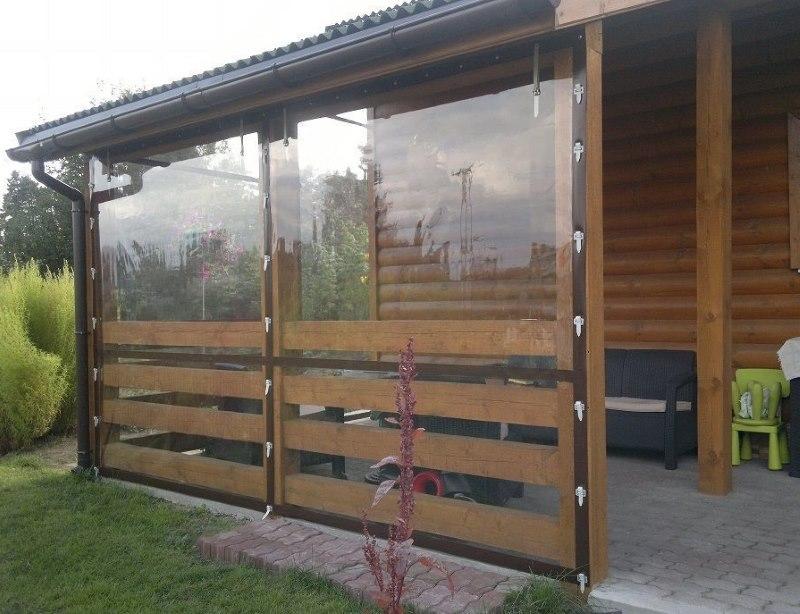 Деревянная веранда частного дома с занавесками из ПВХ