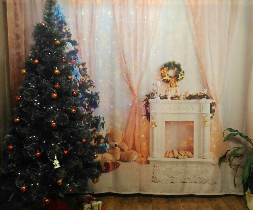 Новогодняя елка на фоне тюля с камином