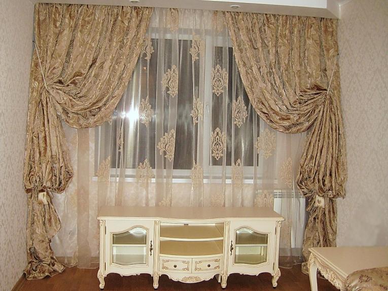 Оформление окна в зале городской квартиры тюлем с вензелями