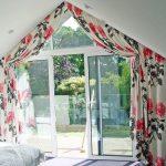 Красивые шторы с цветами для необычного окна в спальне