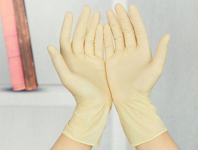 Ладони рук домохозяйки в резиновых перчатках