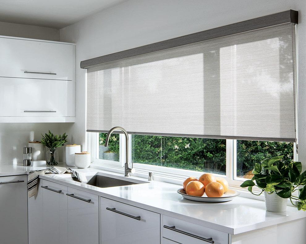 Широкая рулонная штора на кухонном окне