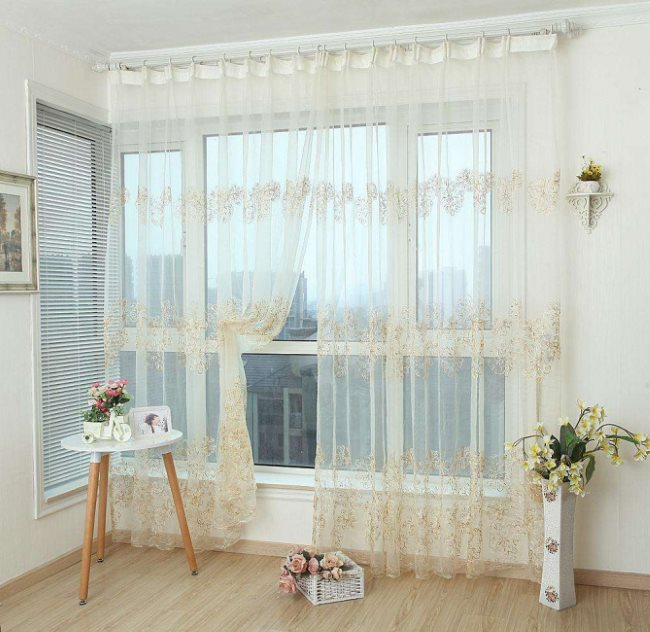 Легкая занавеска из полупрозрачного тюля на большом окне
