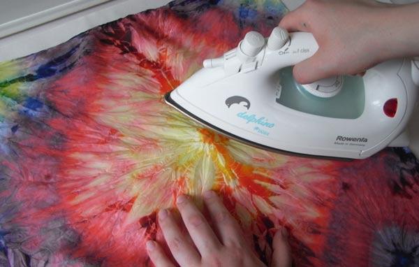 Проглаживание домохозяйкой полиэстеровой шторы с рисунком