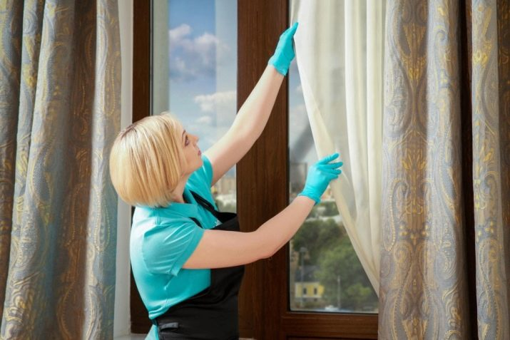 Хозяйка снимает тюль с окна для отбеливания