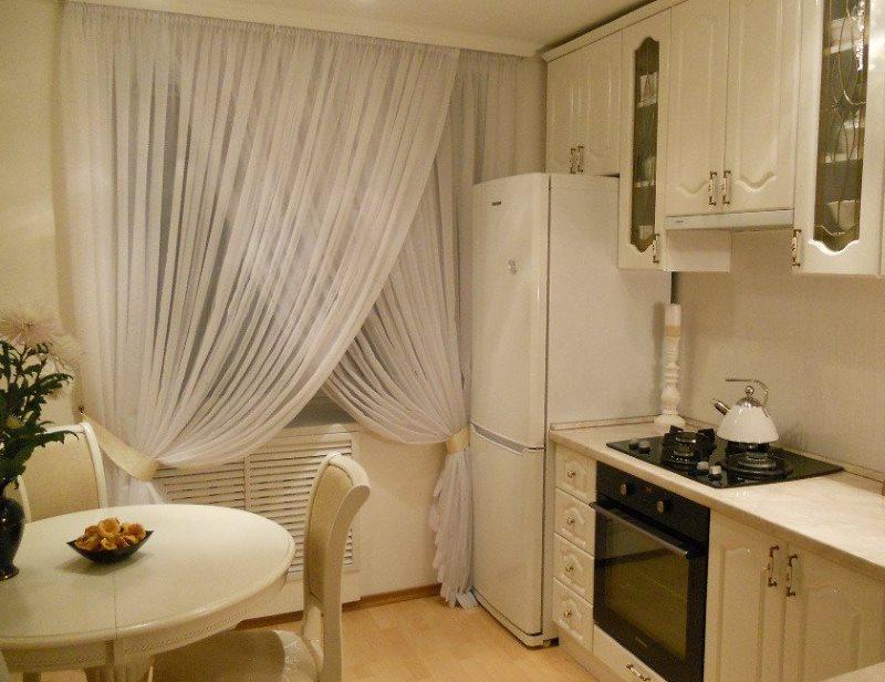 Белые тюлевые занавески на кухонном окне