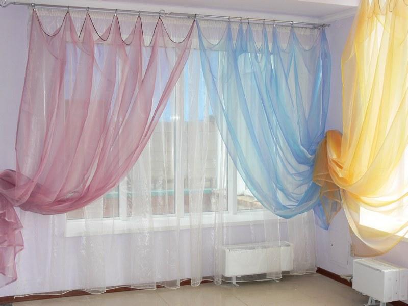 Разноцветные шторы из капрона на окнах в зале
