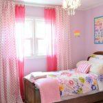 Детская кровать перед окном с тюлем