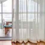 Белая штора и деревянный пол