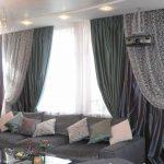 Серый диван перед окном гостиной с плотными портьерами