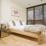 Деревянная кровать в спальне с жалюзи на окнах