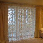 Вуаль с кремовым орнаментом на окне в зале