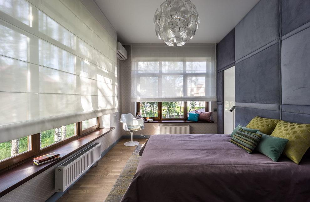 Римские шторы из легкой ткани на больших окнах спальни