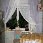 Белые тюлевые шторы на кухонном окне