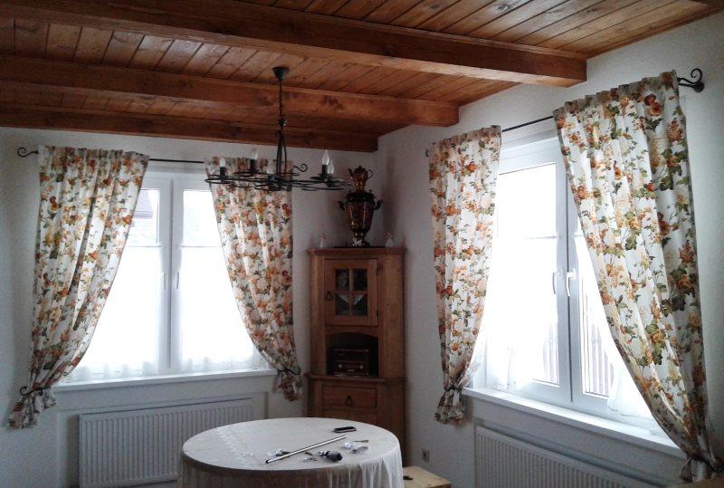 Легкие занавески на окнах зала с деревянным потолком