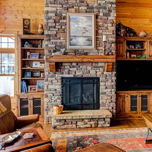 <p><b>Рустик</b><p> Камины данного типа не отличаются богатым убранством. Стиль – примитивный, деревенский, с грубой обработкой камня. Устройства обогрева гармонично впишутся в интерьер со стеновыми панелями из дерева и камня.