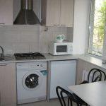 стиральная машина в бежевой кухне