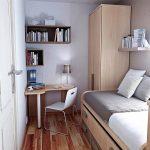 Складной диван и компактный угловой стол в узкой спальне