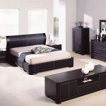 Черная мебель и светлая отделка стен и пола спальни