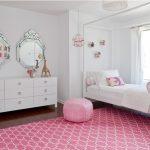 Яркий розовый ковер и пуф эффекто выделяются на фоне белых стен