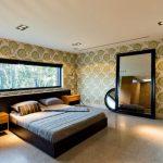 Большая кровать с изголовьем к невысокому окну на всю стену