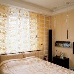 Кровать изголовьем у окна золотистой спальни