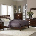 Необычная спальня неправильной формы с изголовьем кровати у огромного окна