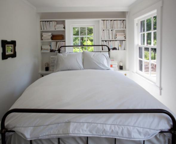 Узкая взрослая спальня с книжными шкафчиками вокруг окна