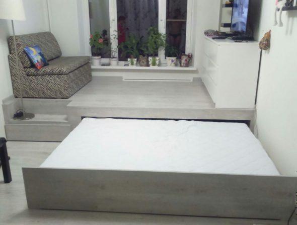 Выдвижная кровать с расположенным на подиуме диваном и телевизором