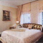 Золотистая кровать в интерьере у окна