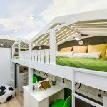 Двойная кровать на верхнем этаже и два стола внизу для двойни