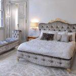 Красивая кровать с мягкой спинкой и длинный мягкий пуфик в спальне
