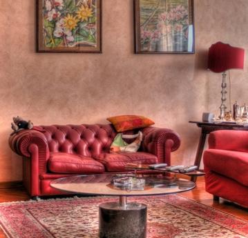Красный диван на фоне терракотовой стены