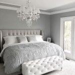 Прекрасная спальня с мягкой кроватью и пуфиком в изножье