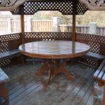 Столик из дерева круглой формы — одно из самых популярных решений для беседки