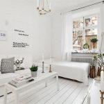 Белая гостиная с белой мебелью вдоль одной стены
