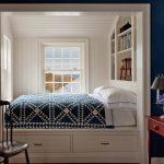 Кровать в нише возле окна с встроенной полкой для книг