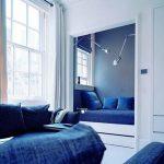 Кровать в закрытой нише в комнате в сине-белых тонах