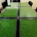 Практичный вариант с искусственной травой, спрятанной под стеклом стола