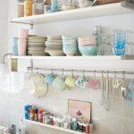 Разноцветная посуда и баночки со специями на открытых полках