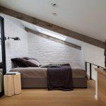 Спальня с кирпичными стенками на мансардном этаже