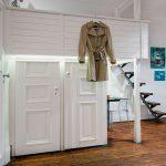 Белая деревянная кровать над встроенным шкафом-гардеробной