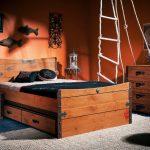Деревянные ящики под кроватью вторят тумбе и комоду